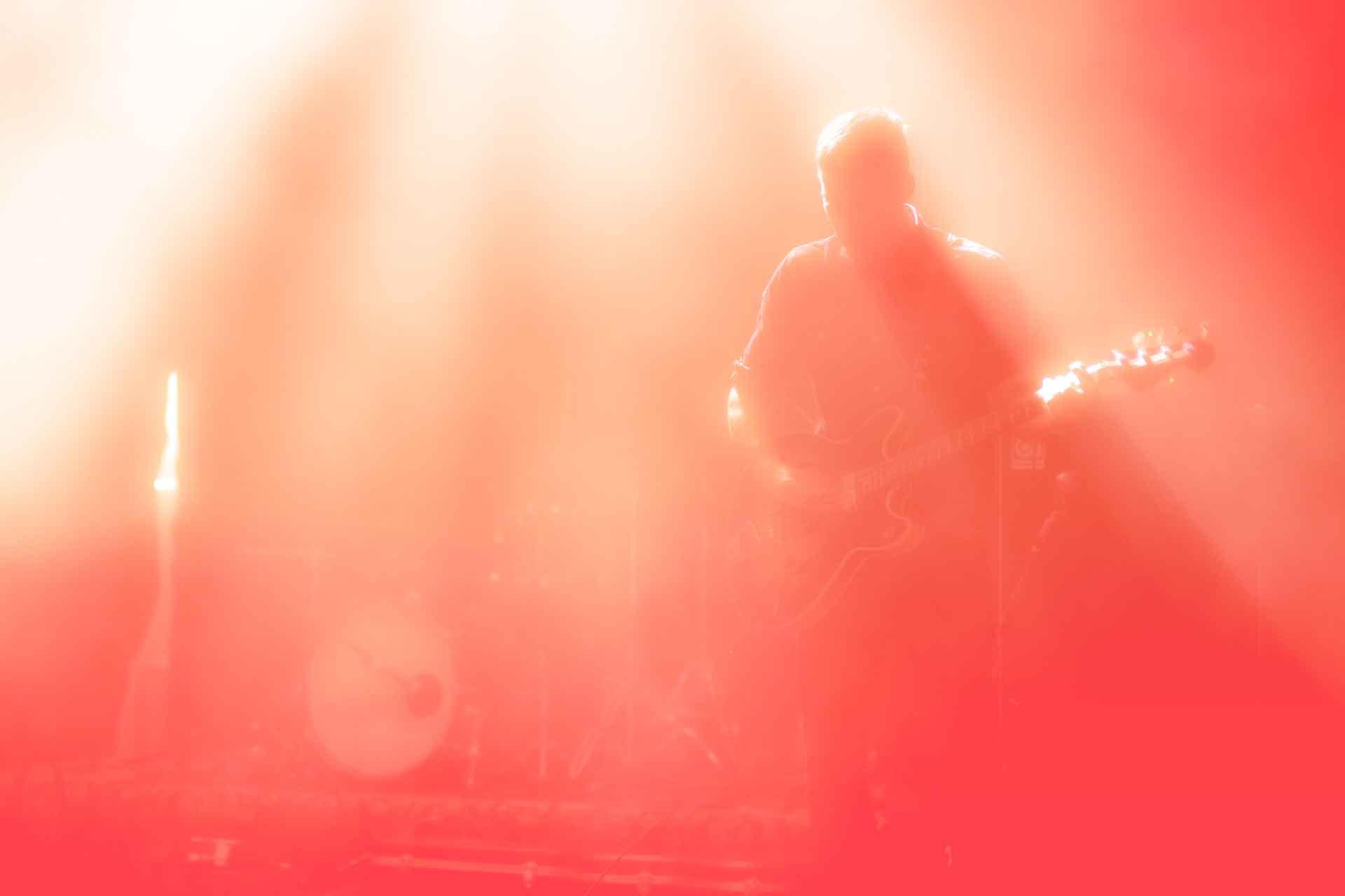 in rot-weissem Licht gefärbte Fotografie eines Mannes mit einer Gitarre und eines Schlagzeugs